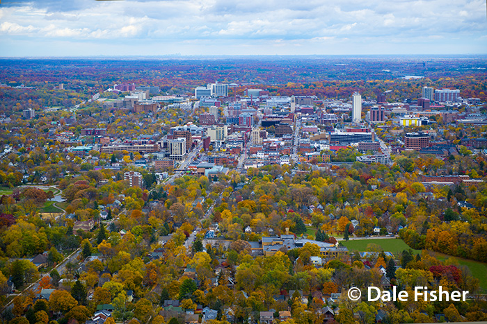 Spectacular Fall Aerial Helicopter Photograph of Ann Arbor which is surrounded by trees.